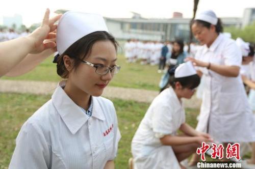 资料图:前辈为医学生戴上护士帽。 泱波 摄